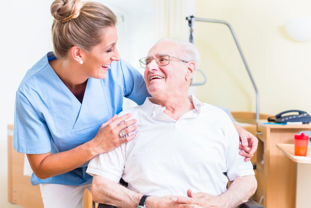 Senior man and old age nurse in nursing home