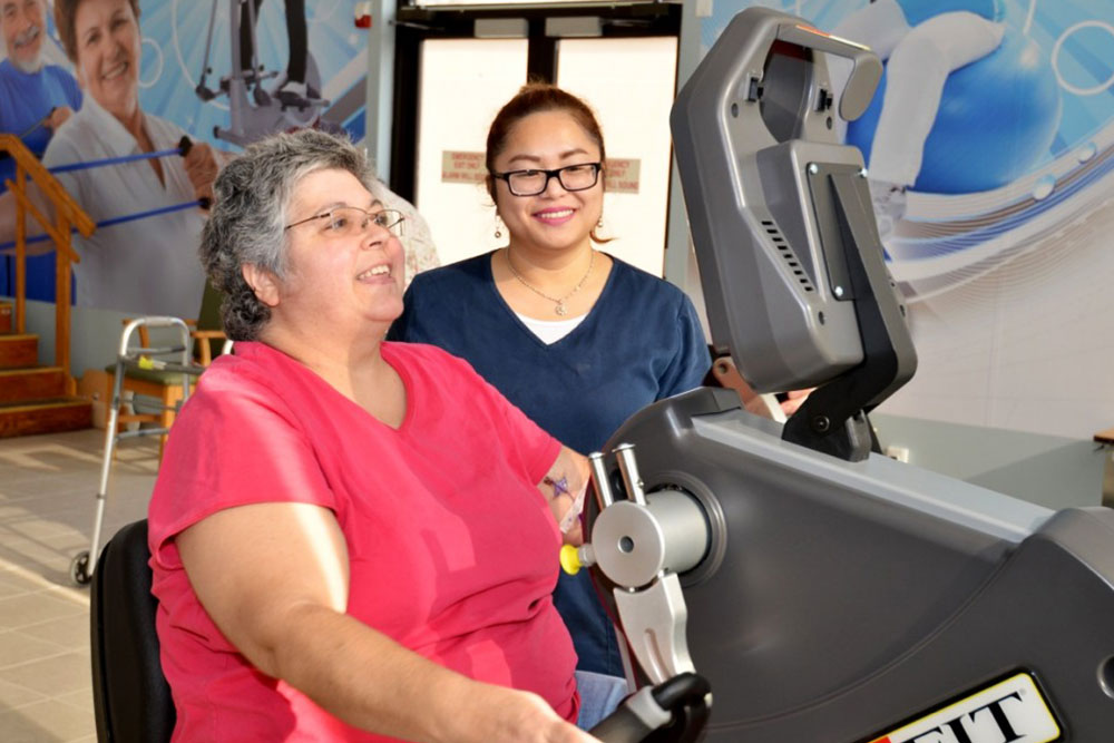 Senior patient working with therapist in exercise room.
