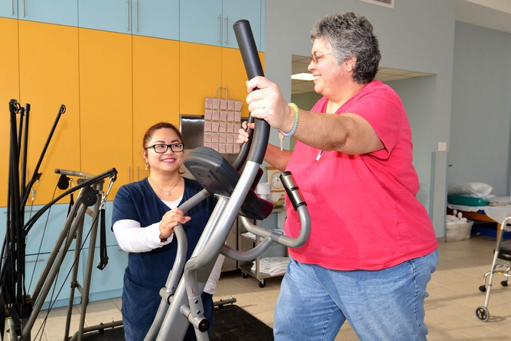 Therapist working with woman on exercise bike.