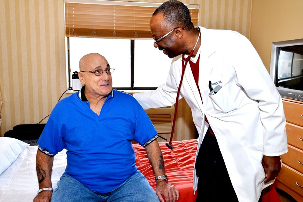 Doctor speaking with senior patient sitting on bed.