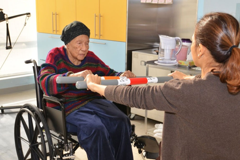 Nurse assisting woman in wheelchair.