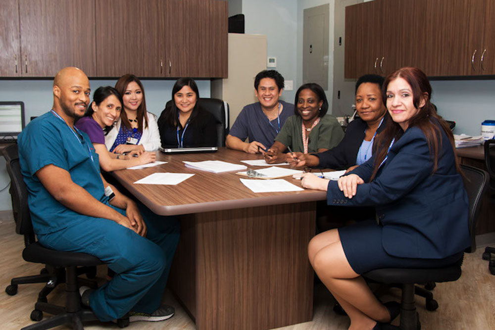 Medical professionals sitting around a wooden conference table.